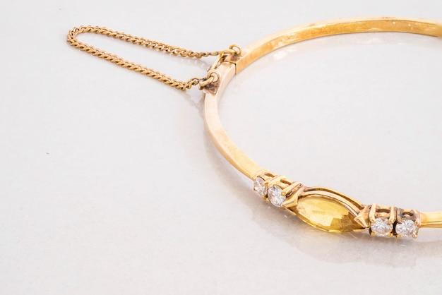 Bracelet or gros plan avec galets jaunes sur fond de pierre de marbre gris Photo Premium