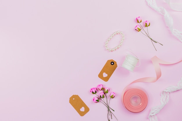 Bracelet de perles; étiquette; ruban; bobine de fil; dentelle et roses artificielles sur fond rose Photo gratuit