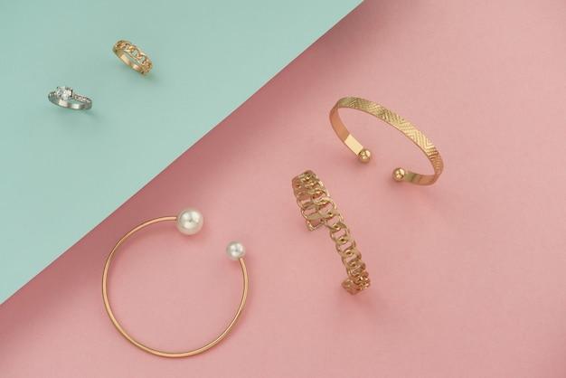 Bracelets Et Bagues De Bijoux En Or Sur Fond Rose Et Bleu Photo Premium