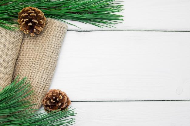 Branche, arbre noël, et, cône, sur, toile jute, sur, blanc, surface vintage Photo Premium