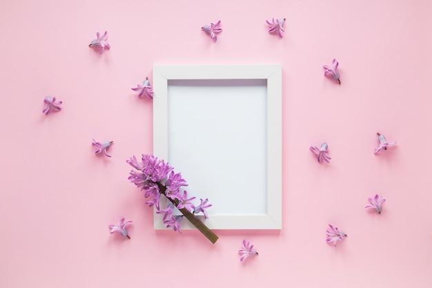 Branche de fleur pourpre avec cadre vide sur la table Photo gratuit