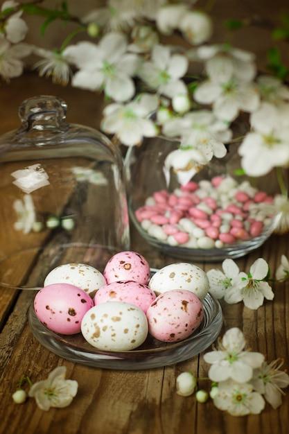 Branche de fleurs printanières et oeufs de bonbons roses colorés pour pâques sur rustique Photo gratuit