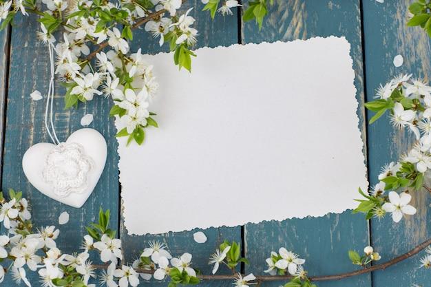 Une branche de pommier en fleurs, un coeur et une feuille de papier vide Photo Premium