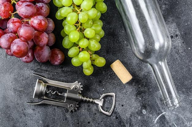 Branche De Raisin Vert Et Rouge, Une Bouteille, Un Tire-bouchon Et Un Bouchon. Concept De Vinification. Fond Noir. Photo Premium