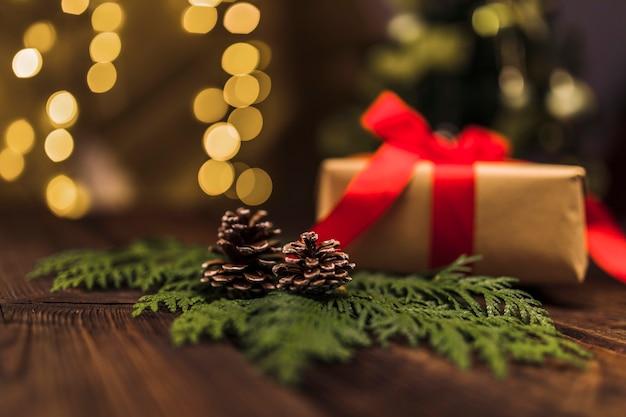 Branche de sapin avec accroc près d'une boîte cadeau avec un arc rouge à bord Photo gratuit