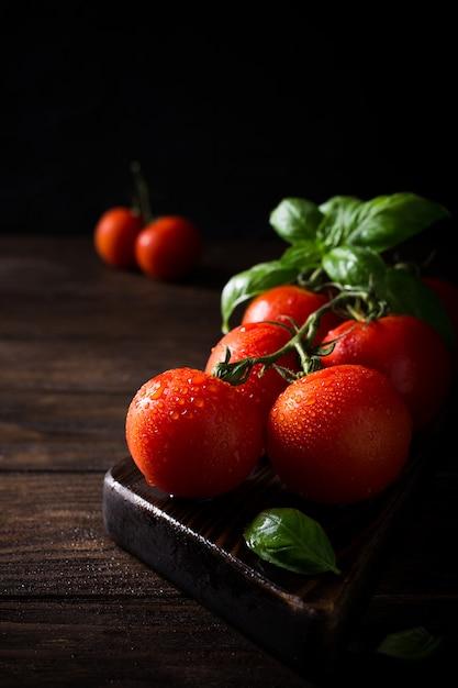 Branche de tomates naturelles mûres et feuilles de basilic Photo Premium