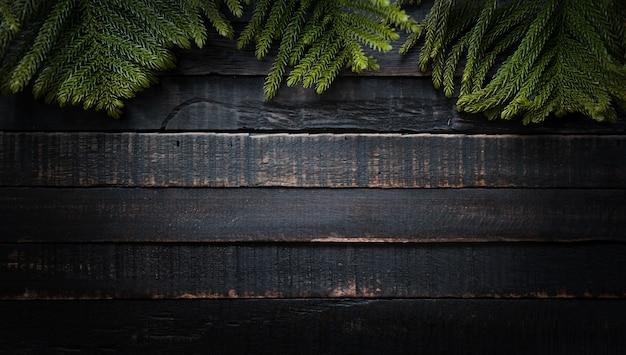 Branches d'arbres de noël sur un fond en bois sombre avec espace de copie. pose à plat Photo Premium