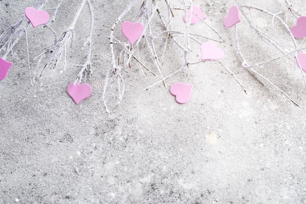 Branches dans la neige avec des coeurs roses sur un fond de béton Photo Premium