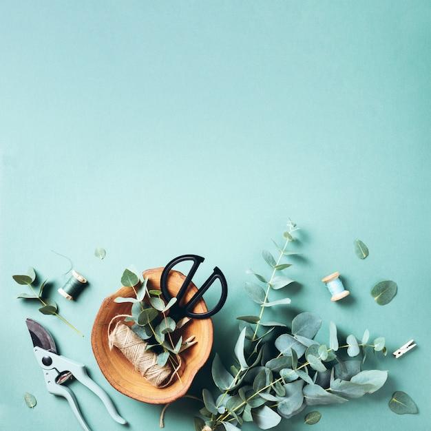 Branches et feuilles d'eucalyptus, sécateur de jardin, ciseaux, plaque de bois sur fond vert Photo Premium