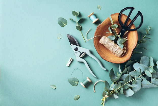 Branches et feuilles d'eucalyptus, sécateur de jardin, ciseaux, plaque de bois Photo Premium