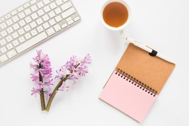 Branches de fleurs avec carnet, clavier et tasse à thé Photo gratuit