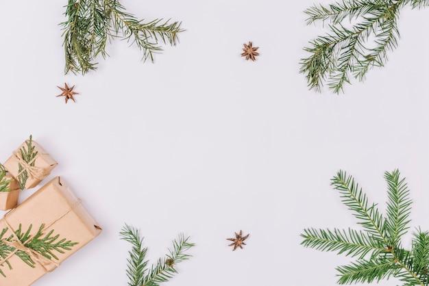 Branches de sapin et cadeaux formant cadre Photo gratuit