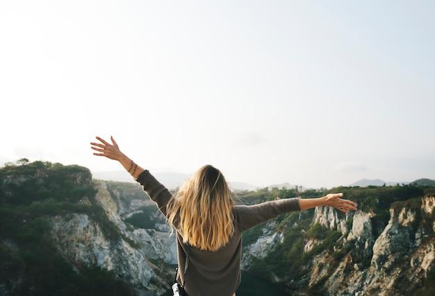 Bras de femme sans soucis tendus sur la montagne Photo gratuit