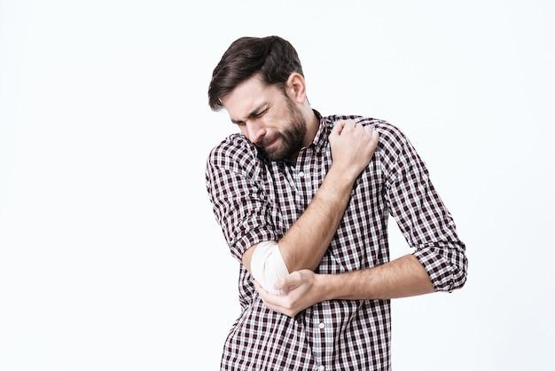 Le bras d'un homme fait mal. son visage grimace de douleur. Photo Premium