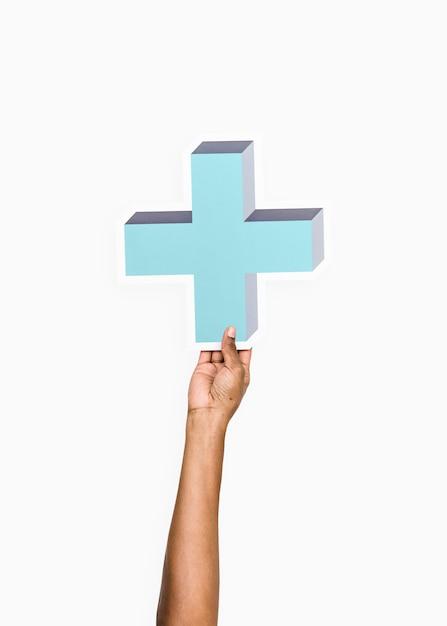 Bras levé et tenant une icône croix bleue Photo gratuit
