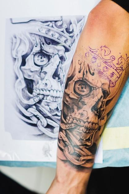 Bras avec tatouage près du croquis Photo gratuit