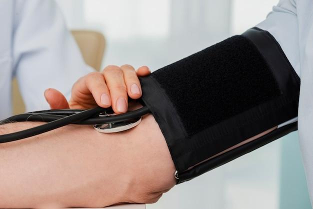 Brassard de tensiomètre au bras du patient Photo gratuit