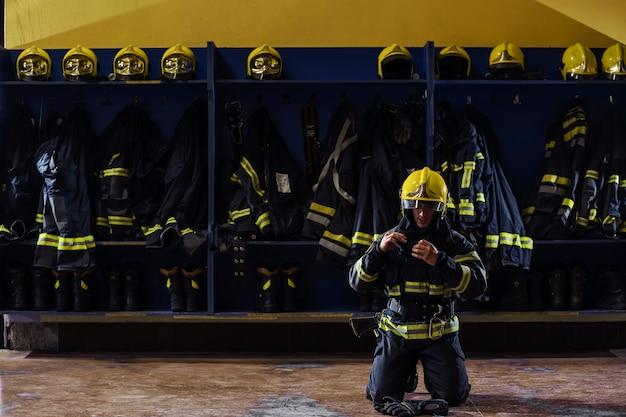 Brave Jeune Pompier En Uniforme De Protection à Genoux Et Mettre Un Casque Sur La Tête. Photo Premium