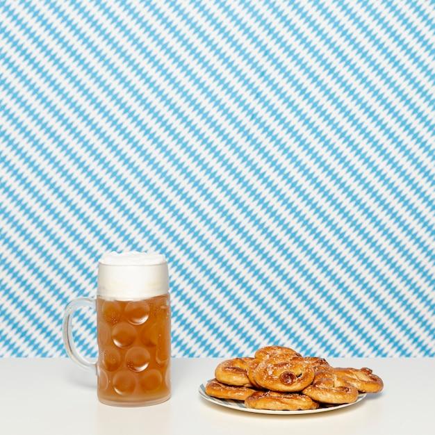 Bretzels mous et bière blonde sur une table blanche Photo gratuit