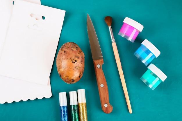 Bricolage des oeufs de pâques en carton et timbre de pomme de terre, carte de voeux de pâques sur fond vert. Photo Premium