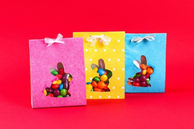 Bricolage de pâques emballant des bonbons dans un sac avec une silhouette de lapin découpée sur un fond rouge. Photo Premium