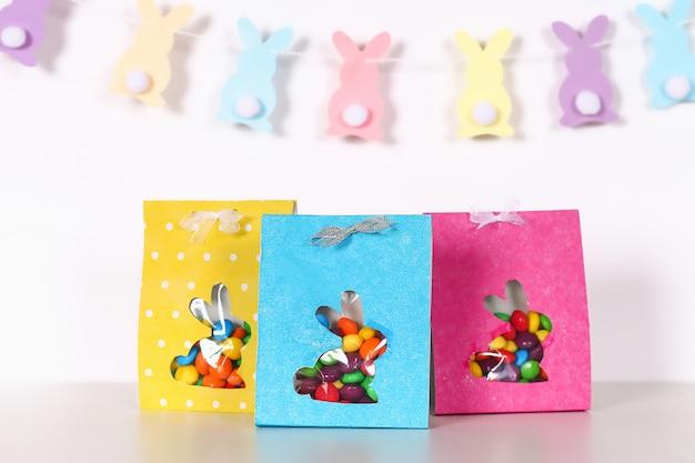 Bricolage de pâques emballant des bonbons de paquet dans un sac avec une silhouette de lapin découpée sur un fond blanc. Photo Premium