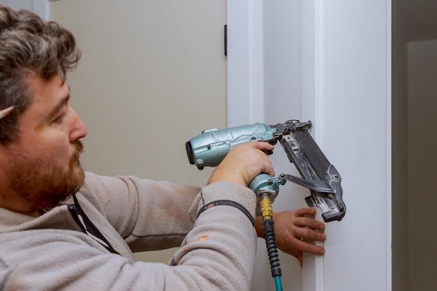 Bricoleur De Construction à L'aide D'un Pistolet à Clous à Air, Installation De La Porte Intérieure De L'appartement Photo Premium