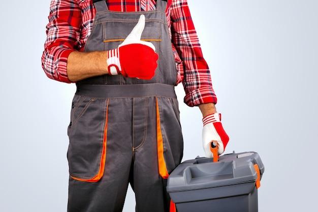 Bricoleur Avec Le Pouce De La Boîte à Outils Sur Fond Gris. Photo Premium