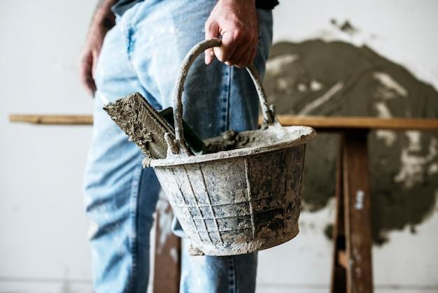 Bricoleur tenant un panier de ciment pour la construction Photo gratuit