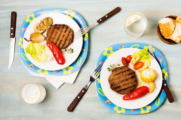 Bright dîner servi avec des steaks et des légumes Photo gratuit