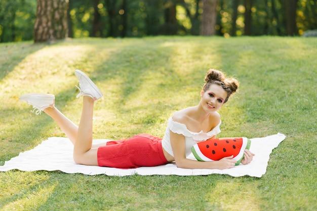 Brillante et jeune fille se trouve sur un plaid blanc sur une pelouse dans un parc Photo Premium