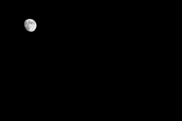 Brillante petite lune blanche sur un ciel noir la nuit Photo Premium