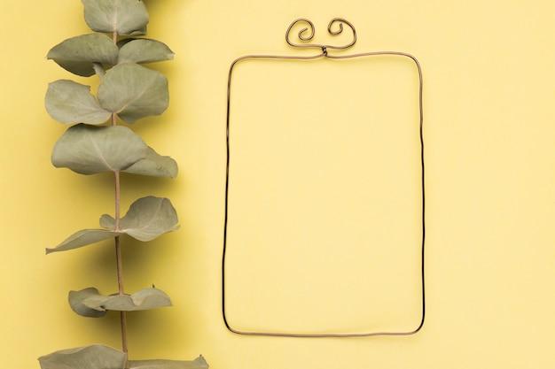 Brindille séchée près du cadre rectangulaire métallique sur fond jaune Photo gratuit