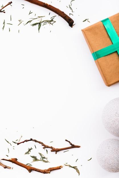 Brindilles, boules de neige et boîte à cadeaux Photo gratuit