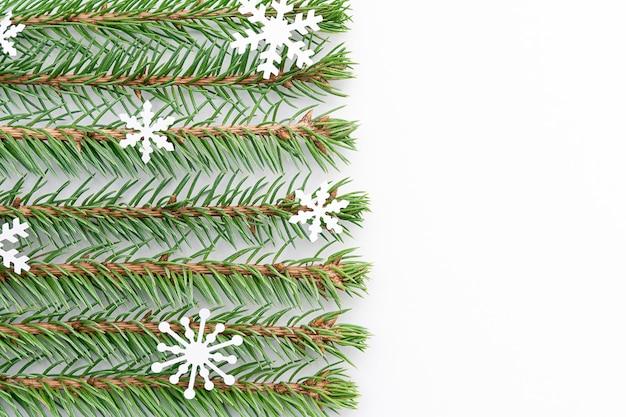 Les brins d'épinette bleue avec des flocons de neige sont disposés horizontalement dans des rangées paires sur un fond blanc. Photo Premium