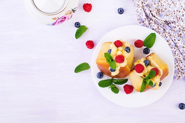Brioches Savoureuses Au Rhum Décorées De Crème Fouettée Et De Petits Fruits Photo Premium