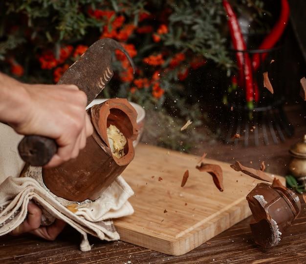 Briser un pot de poterie avec un grand couteau. Photo gratuit