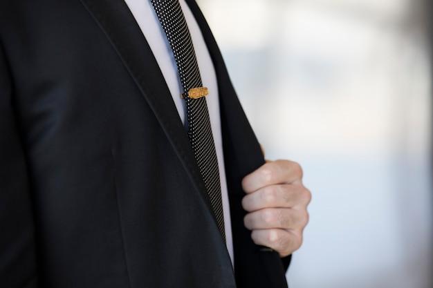 Broche Dorée Sur La Cravate D'un Homme En Costume. Photo gratuit