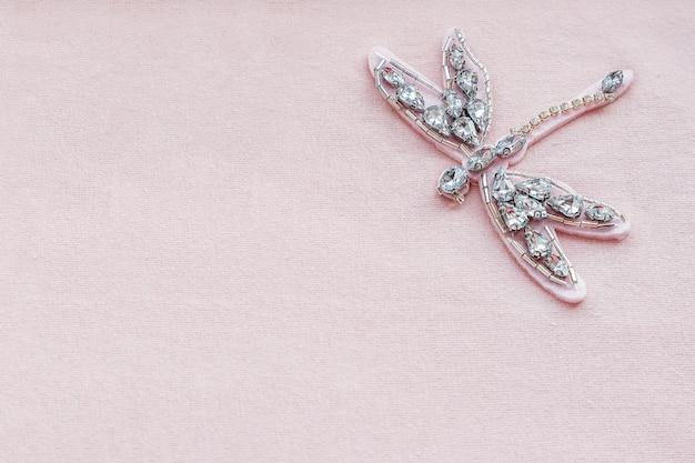 Broche libellule de strass et de perles sur fond de tissu rose Photo Premium
