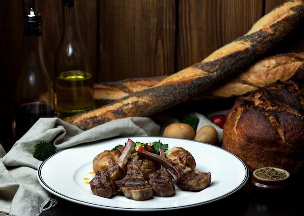 Brochette De Côtes D'agneau Servie Avec Pommes De Terre Grillées Et Salade Photo gratuit