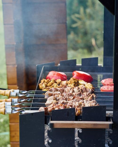 Brochette de shashlik au barbecue avec ailettes et tomates avec poivron rôti au charbon sur brochette Photo Premium