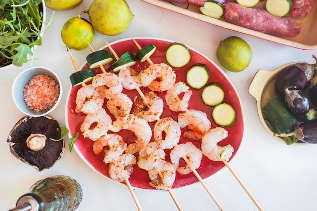 Brochettes de crevettes servies avec des légumes et des fruits Photo gratuit