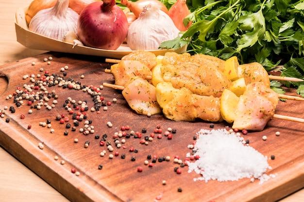 Brochettes de poulet crues marinées au citron sur une planche de bois Photo Premium