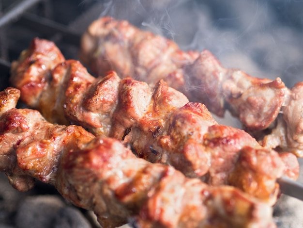 Brochettes de viande grillées sur les braises, avec de la fumée. la nourriture de rue. Photo Premium