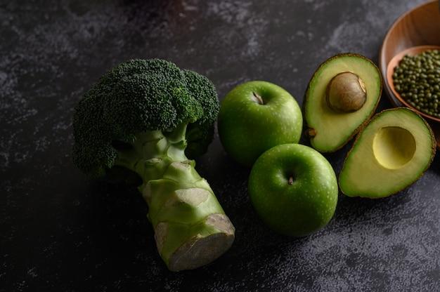 Brocoli, Pomme Et Avocat Sur Un Sol En Ciment Noir. Photo gratuit
