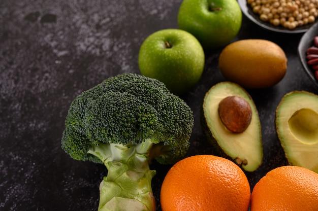Brocoli, Pomme, Orange, Kiwi Et Avocat Sur Un Sol En Ciment Noir. Photo gratuit