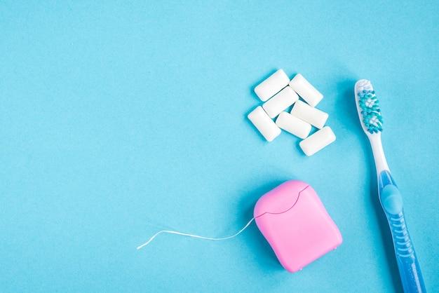 Brosse à Dents, Fil Dentaire Et Gomme Sur Fond Bleu. Nettoyage Et Protection Des Dents Photo Premium
