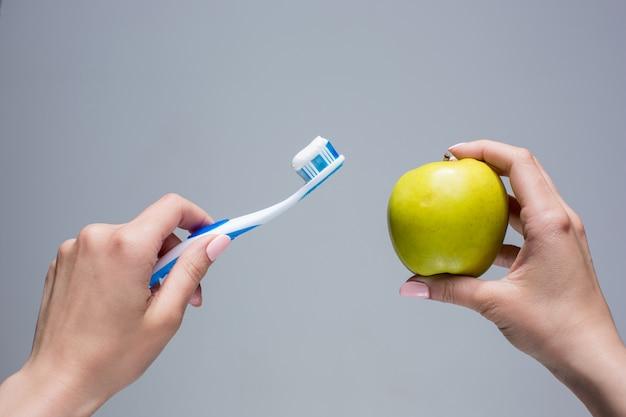 Brosse à Dents Et Pomme Dans Les Mains De La Femme Sur Gris Photo gratuit