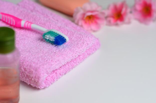 Brosse à dents rose sur une serviette rose Photo Premium
