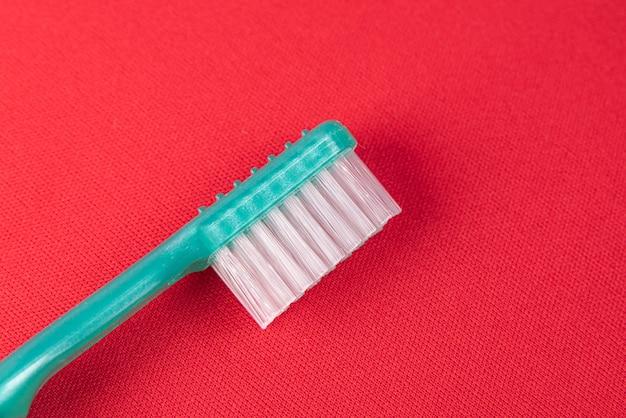 Brosse à Dents Turquoise Sur La Surface Rouge Photo gratuit
